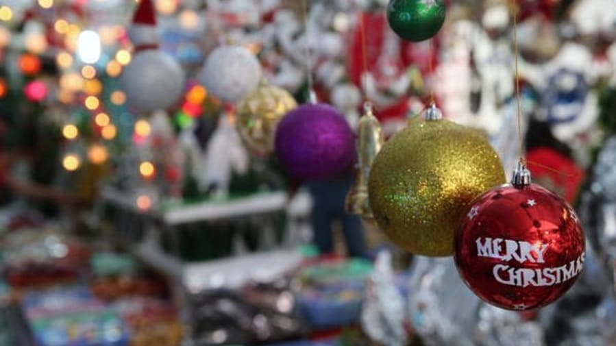 colourful hanging baubles in sharp focus with a background of the Christmas market