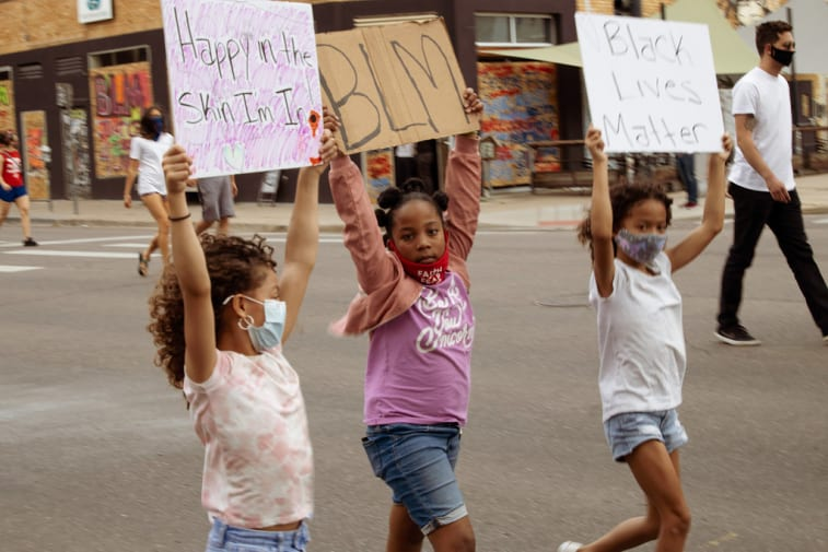 3 young girls marching with placards