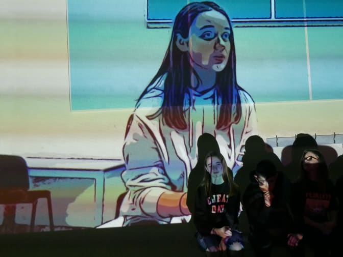 photograph of three students sat against a wall with projection of an image of student in background