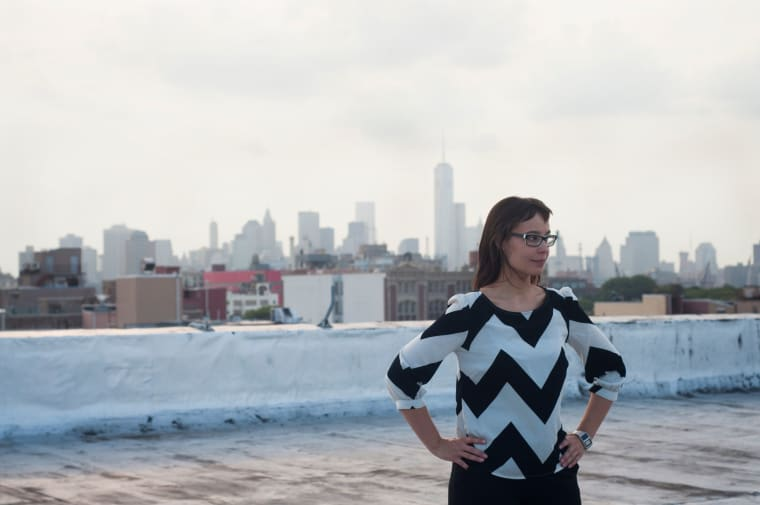 A photo of a young woman with a black and white top and hands on hips outdoors in an urban landscape with a white wall and city scene behind her