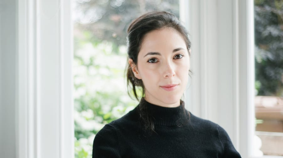 Portrait of Chiara, who has fair skin and black hair, wearing a black turtleneck
