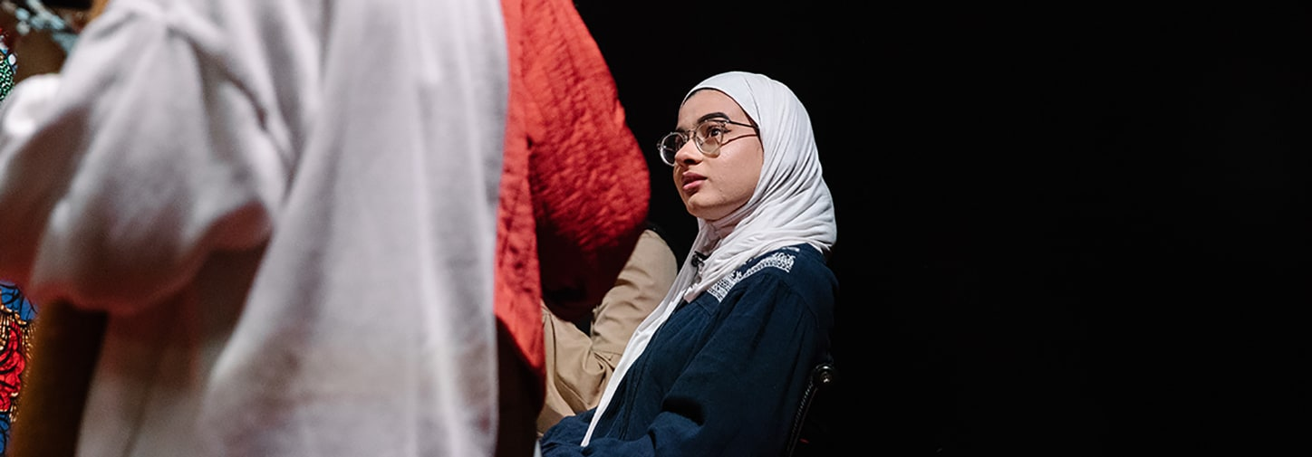 Woman in hijab with glasses listening in crowd in dark room
