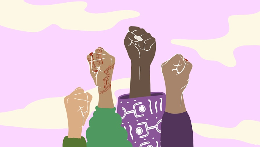 Four women of diverse background and cultures holding their fists up in unity.