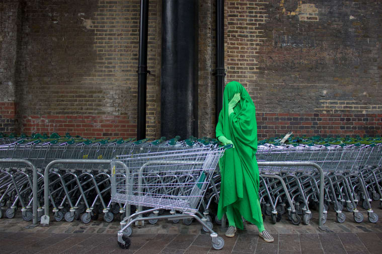 Person covered in green pushing shopping trolley