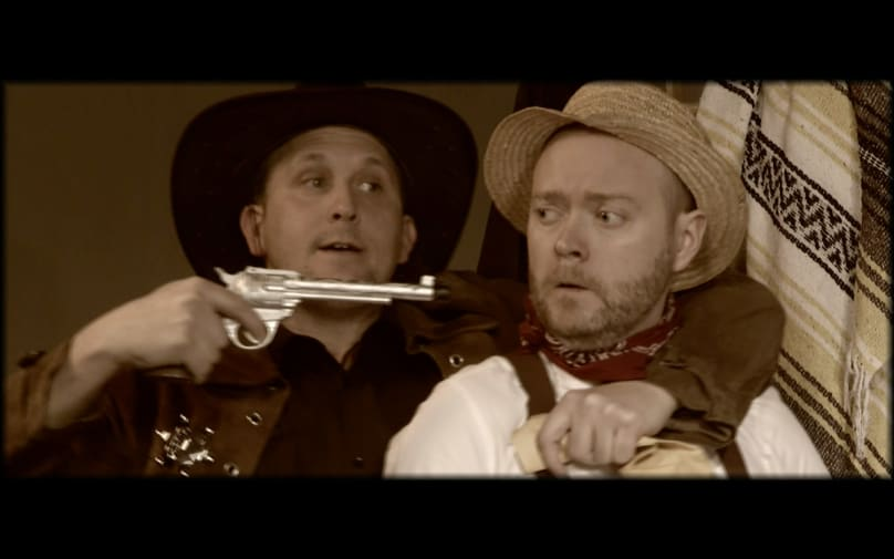 Man in cowboy-style hat holds a gun to the head of a man.