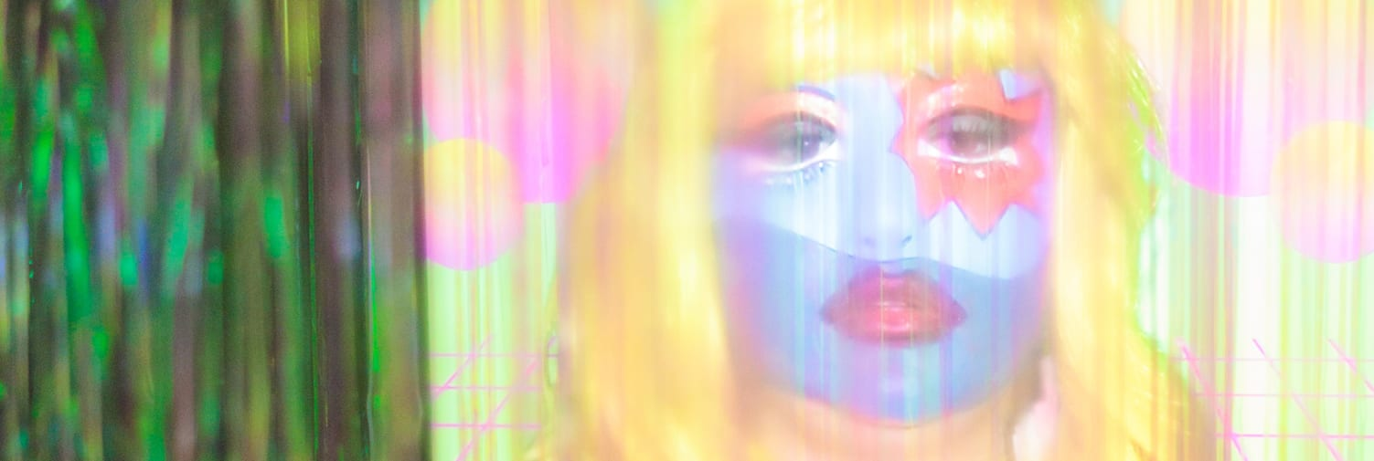 Close-up photograph of a screen showing a yellow and pink video of a woman in blue and red face make-up, wearing a yellow wig, is viewed through a curtain of iridescent green plastic streamers.