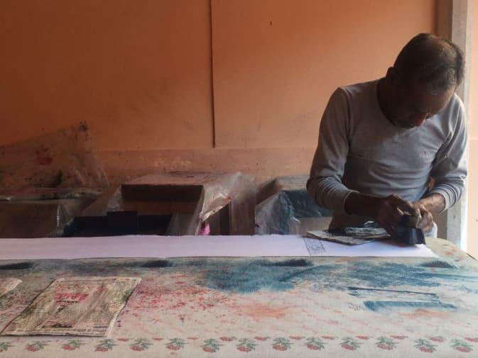 Man block-printing fabric