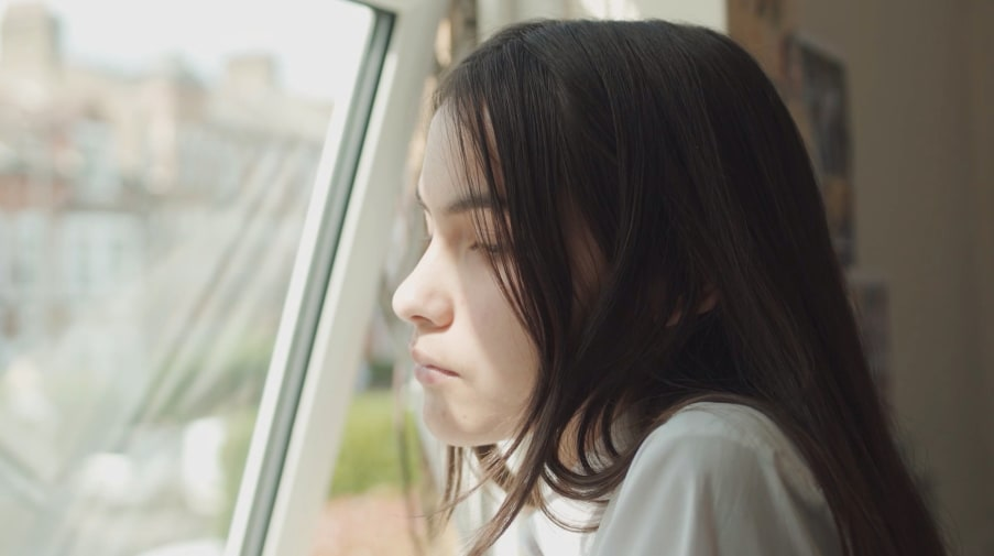 A young girl stares out of the window.