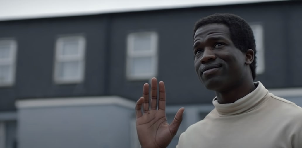 A black man outside waving up at someone, with a housing estate in the background