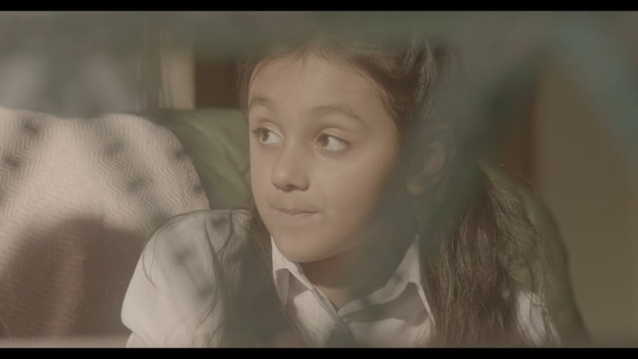a film screen shot of a little girl looking to the side