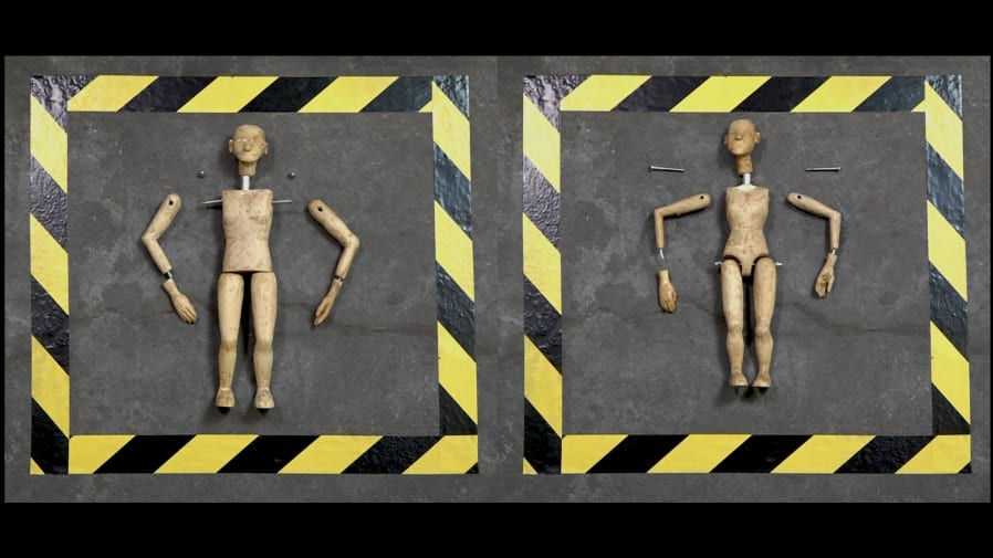 Two wooden puppets with limbs taken apart, surrounded by black and yellow tape