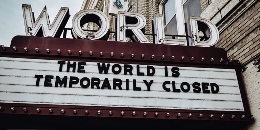 Image depicts a cinema board which reads: 'The world is temporarily closed.'