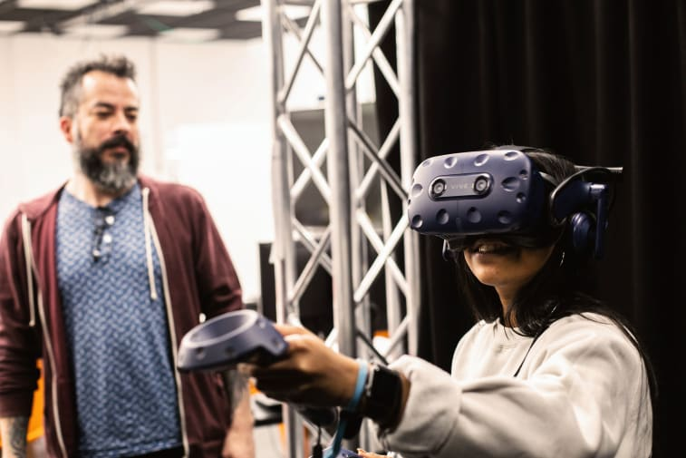 Technician standing next to a student wearing a virtual reality headset