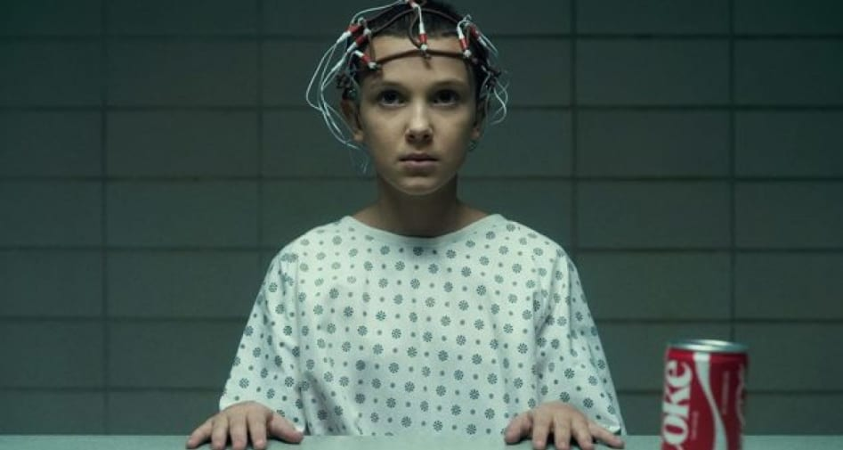 Still from the television programme Stranger Things, showing Eleven sat with an electrode helmet by a table with a Coke can.