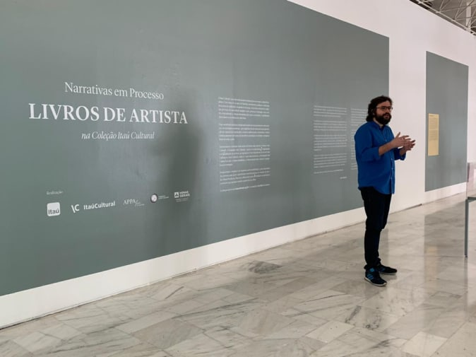 A casually dressed professor shot against a large internal grey wall with Portuguese writing