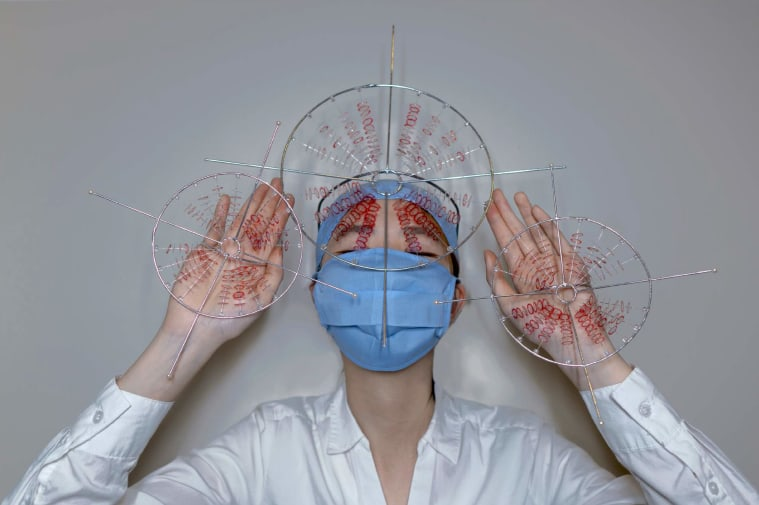 Figure wearing surgical mask and perspex and red thread appendages