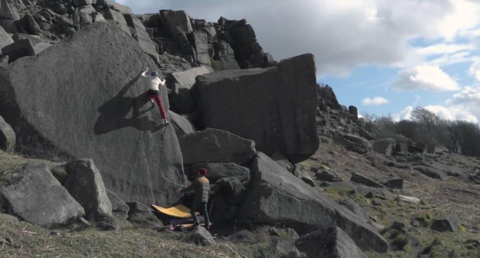 Woman climbs rock-face in mountain.