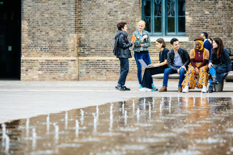 Students talking outside fountain at Central Saint Martins, UAL