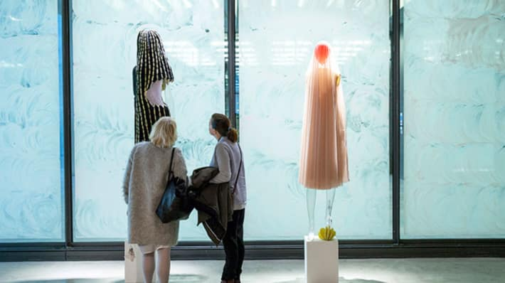 Two people looking at garments on mannequins