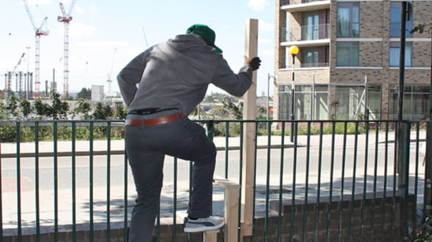 Man climbing over a fence