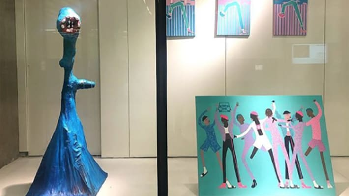 Photograph of a blue sculpture and paintings of illustrated people dancing on display in the Window Gallery at Central Saint Martins