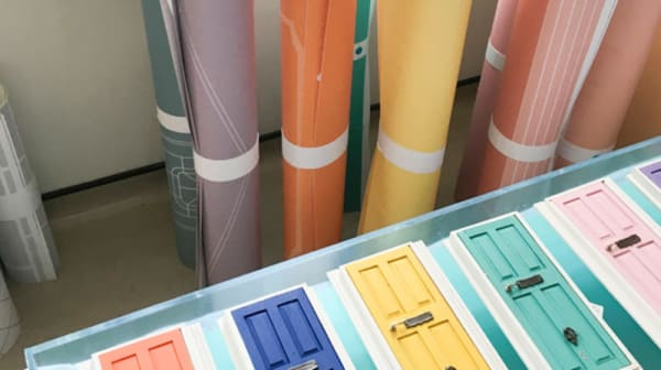 Colourful rolls of paper and photos of different colour front doors
