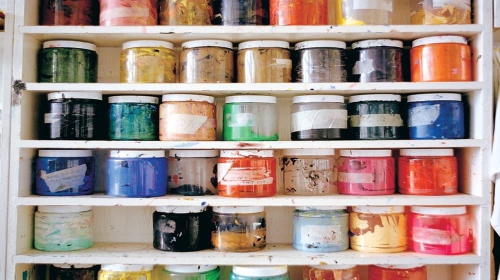 Shelves of coloured paint pots