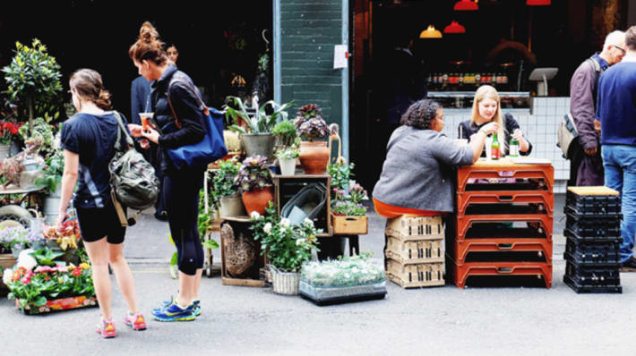 Two female students looking at a flower stall