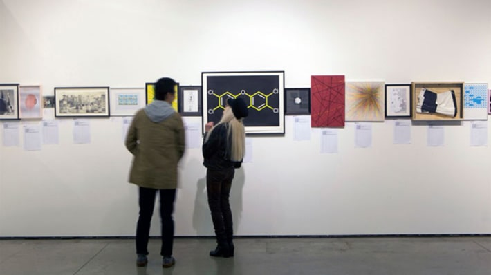 People looking at donations to the Postgraduate Art Auction on display in the Lethaby Gallery