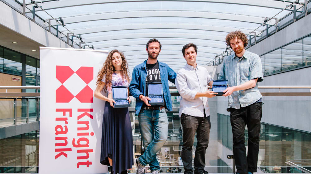 Four student prize winners standing with their prizes