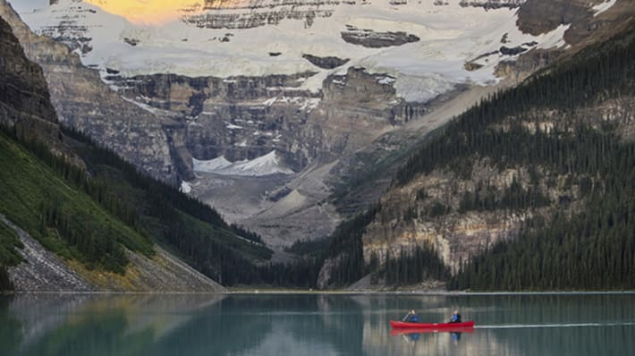 Photo of a red canoe with two people in on the water of Lake Louise in Aberta, Canada with mountains surrounding