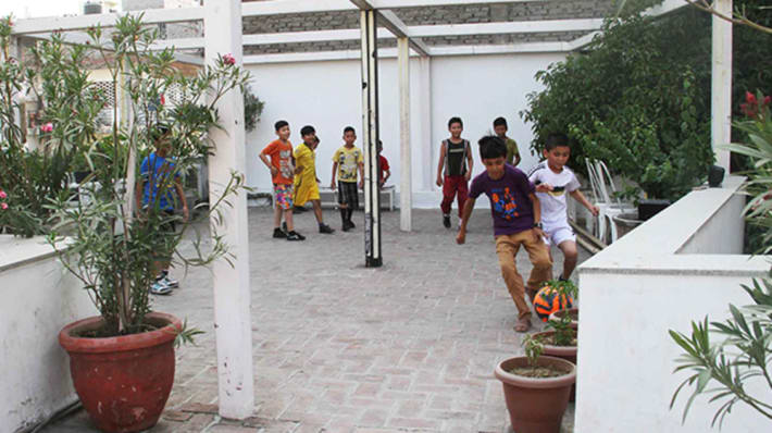 Photo of a group of young boys playing football in a courtyard