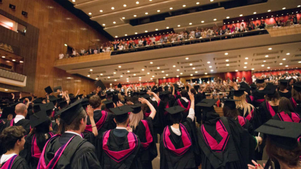 Students and guests filling the auditorium for a graduation ceremony