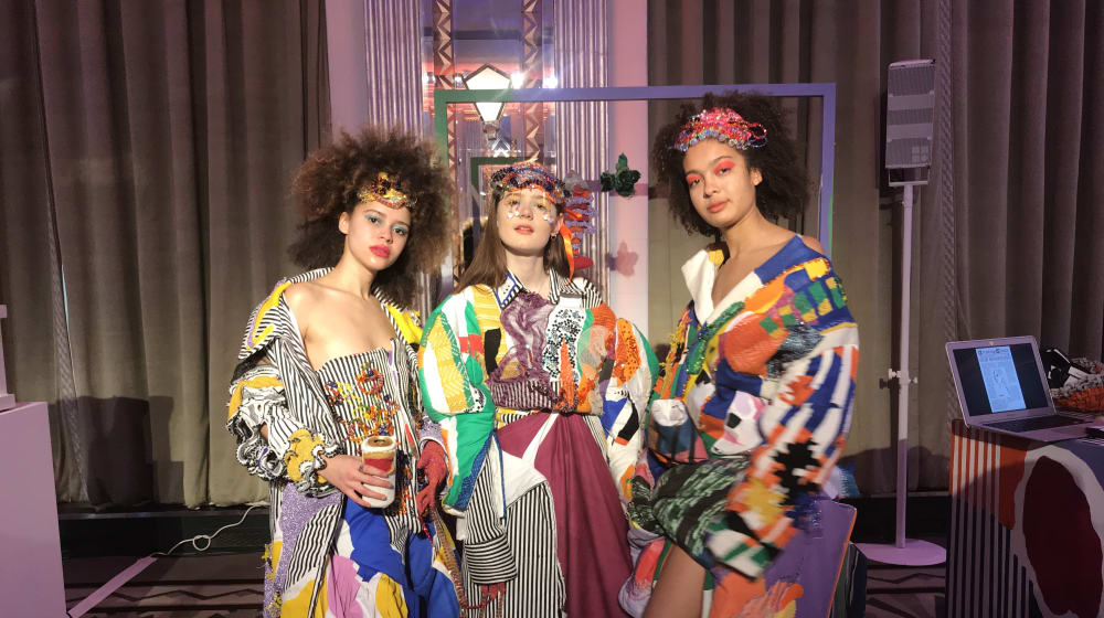 Three people wearing brightly coloured designs