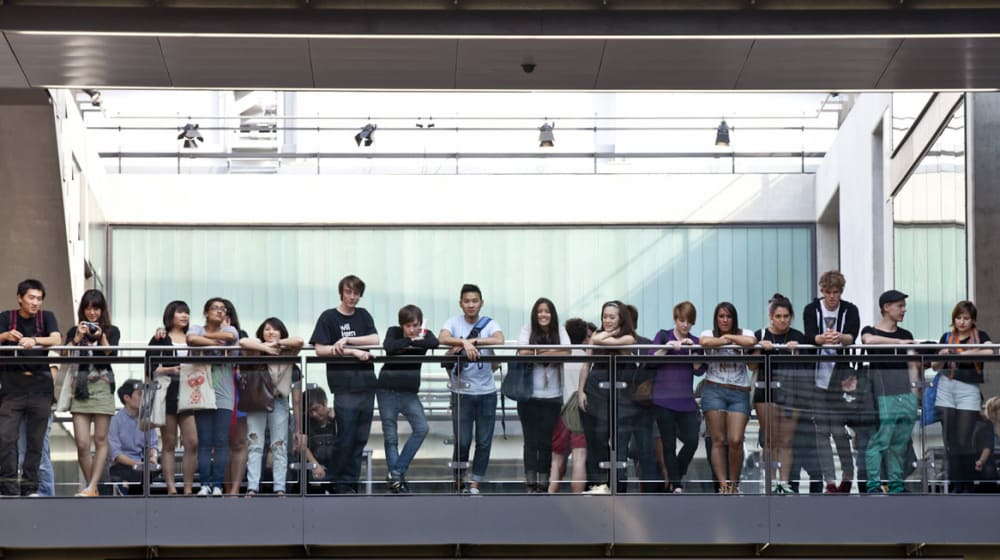 A row of people stood on the top floor inside Central Saint Martins