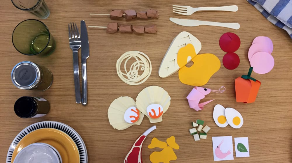 Pieces of food made out of paper lying on a table with cutlery