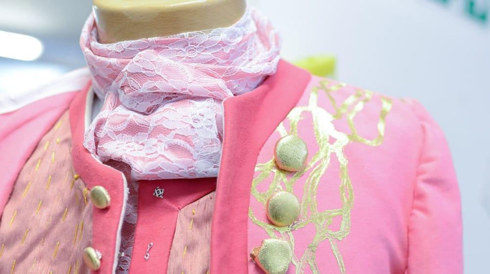 Close up shot of a pink dress coat with gold trim