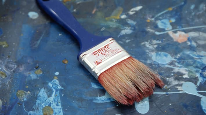 Paint brush laid on top of painting