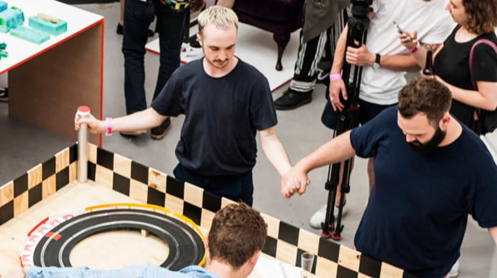 photograph of two men holding hands while powering toy cars by human energy