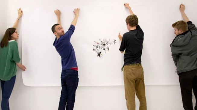 Photo of four people handing a piece of art on a white wall
