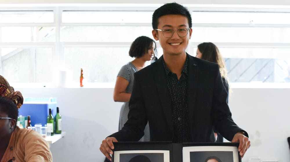 Image of Student Calvin Ma with his photographic work holding two frames in his hands.