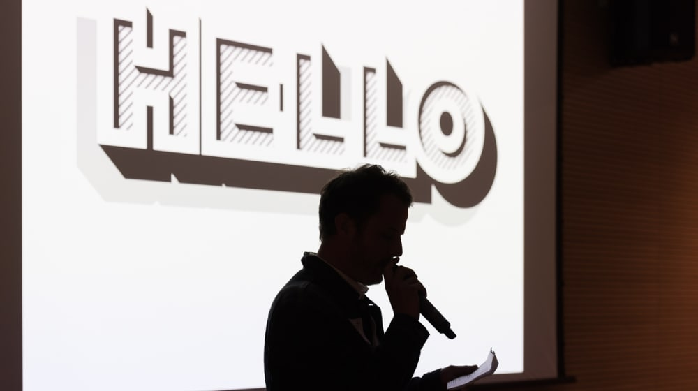 Silhouette of somebody speaking into a microphone