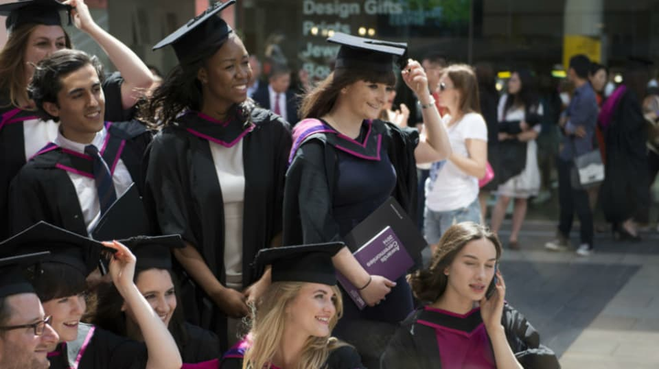 A group of graduates have their picture taken in their graduation robes.