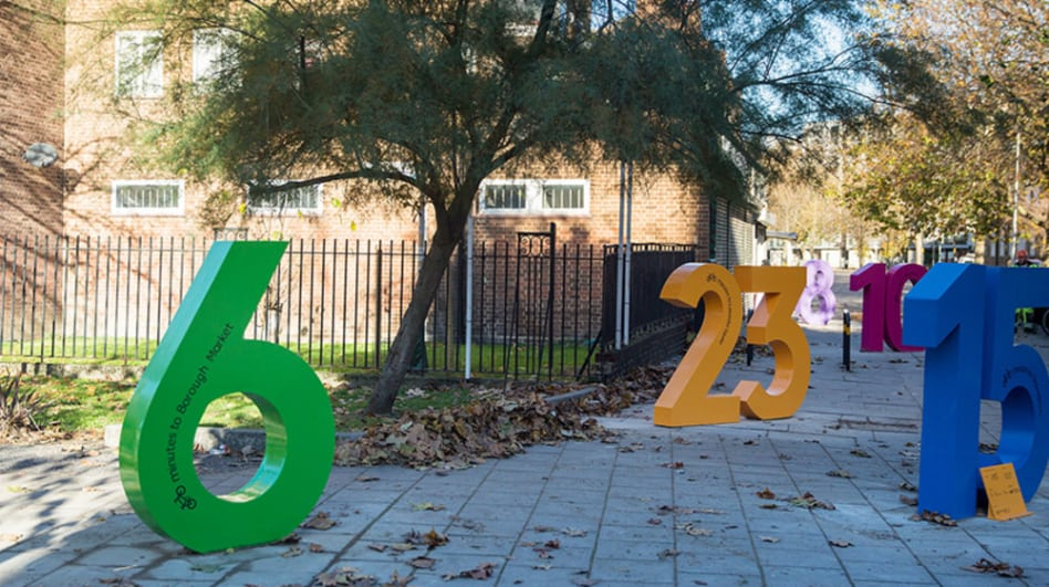 An installation of large colourful numbers designed by LCC graduates and placed around the Santander Cycle Hire docking station.