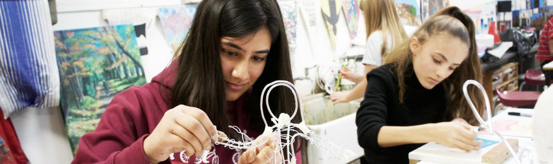 Students working in a classroom making wire figure sculpture.