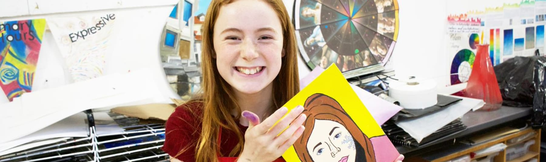 Girl holding up a painted self portrait.