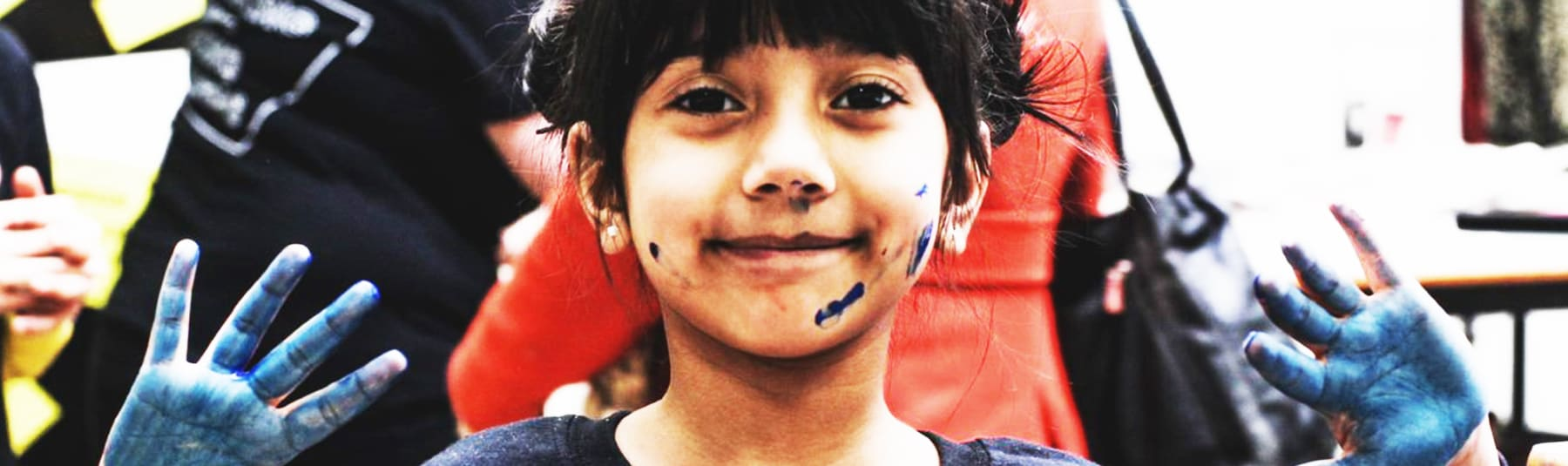 A Young girl holds up her hands showing that they are covered in blue paint, she also has a few paint marks on her face.