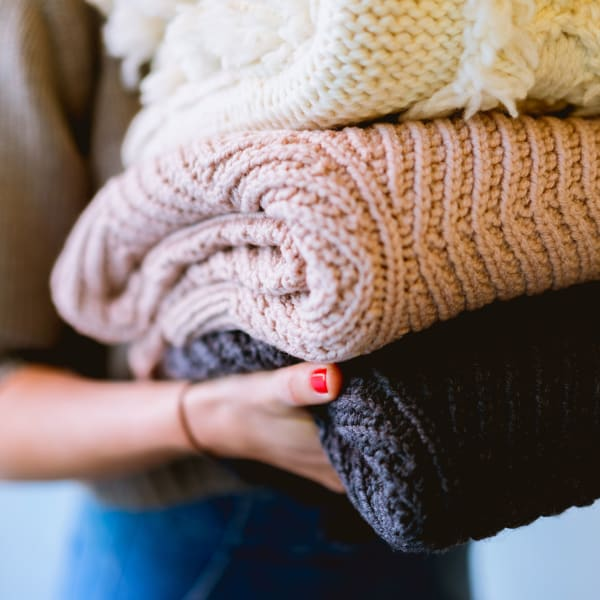 Student holding knitted garments