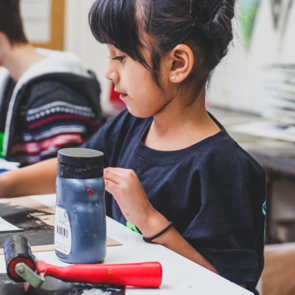 Young girl working with printing inks in a classroom.
