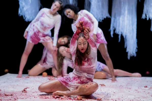 A group of dancers tearing fruit on stage. Their white dresses stained by fruit